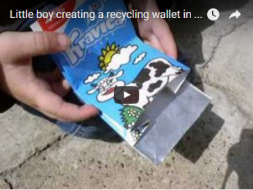 Little boy creating a milk carton wallet